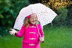Petite fille avec le parapluie sous la pluie Photos stock