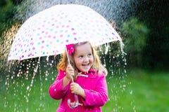 Petite fille avec le parapluie sous la pluie Photo stock