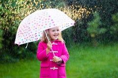 Petite fille avec le parapluie sous la pluie Images libres de droits