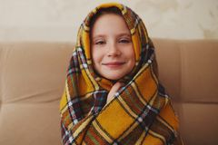 Petite fille avec le plaid à la maison photographie stock