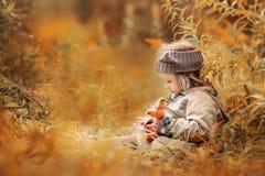 Petite fille avec le renard de peluche dans la forêt d'automne Image libre de droits