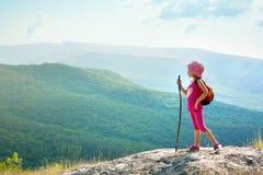Petite fille avec le sac à dos se tenant sur le bord de falaise Image stock