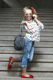 Petite fille avec le sac dans la pose de lunettes de soleil Photo stock