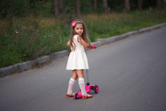 Petite fille avec le scooter sur la route Images stock