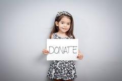 Petite fille avec le signe de donations image stock