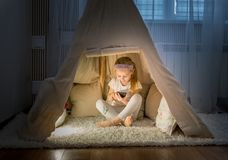 Petite fille avec le smartphone se reposant dans la tente de tipi Photos libres de droits