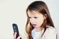 Petite fille avec le téléphone portable. Photos libres de droits