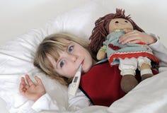 Petite fille avec le thermomètre clinique Image stock