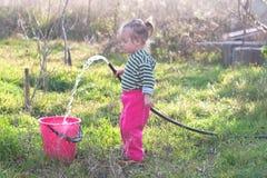 Petite fille avec le tuyau dans le jardin Photo stock