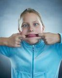 Petite fille avec le visage idiot. Photo libre de droits