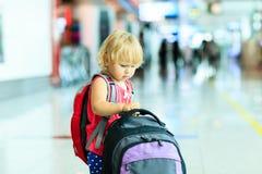 Petite fille avec le voyage de valise dans l'aéroport Photos stock