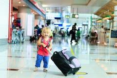 Petite fille avec le voyage de valise dans l'aéroport Photo stock