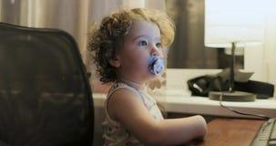 Petite fille avec les cheveux bouclés et une tétine dans sa bouche se reposant près du moniteur d'ordinateur banque de vidéos