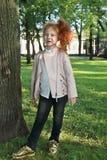 Petite fille avec les cheveux rouges dans la veste en cuir Photos stock