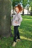 Petite fille avec les cheveux rouges dans la veste en cuir près de l'arbre Image libre de droits