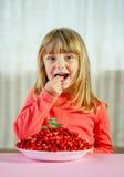 Petite fille avec les fraisiers communs, Images stock