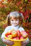 Petite fille avec les légumes frais dans le jardin Image libre de droits