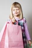 Petite fille avec les sacs à provisions et la lucette Photos stock