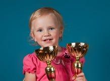 Petite fille avec les trophées d'or photographie stock libre de droits