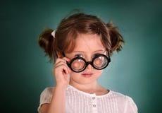 Petite fille avec les verres à bouteilles épais Photographie stock
