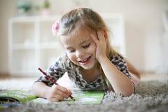 Petite fille avec livre de coloriage Images libres de droits