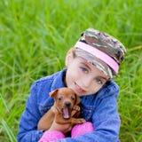 Petite fille avec pinscher de mascotte de chiot d'animal familier le mini photographie stock libre de droits