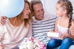 Petite fille avec plaisir recevant un cadeau de ses grands-parents Photographie stock