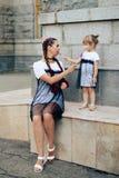 Petite fille avec sa mère dans les robes avec la sucrerie Photo libre de droits