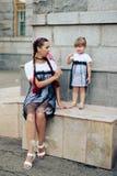 Petite fille avec sa mère dans les robes avec la sucrerie Photographie stock