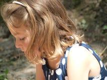 Petite fille avec ses cheveux vers le bas et regardant vers le bas images libres de droits