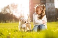 Petite fille avec son chiot Photos libres de droits