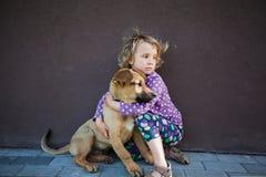 Petite fille avec son chiot Photographie stock libre de droits