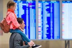 Petite fille avec son information de vol de fond de père à l'aéroport Photographie stock libre de droits