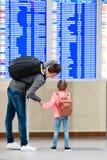 Petite fille avec son information de vol de fond de père à l'aéroport Photo stock