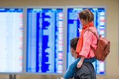 Petite fille avec son information de vol de fond de père à l'aéroport Image stock