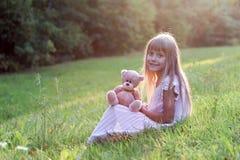 Petite fille avec son ours de nounours d'ami Photo stock