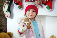 Petite fille avec un biscuit de Noël d'homme de gingembre Photographie stock libre de droits