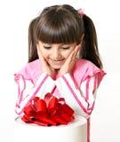 Petite fille avec un cadeau grand Photos stock