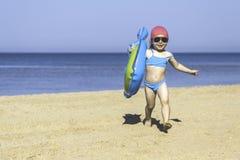 Petite fille avec un cercle sur une plage de sable de mer images libres de droits