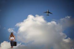 Petite fille avec un chat se reposant sur une valise dans les nuages Photo stock