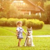 Petite fille avec un chien de traîneau de chien Photographie stock libre de droits