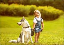 Petite fille avec un chien de traîneau de chien Photos stock