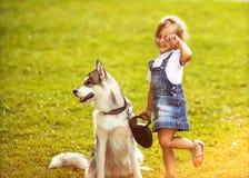 Petite fille avec un chien de traîneau de chien Images libres de droits