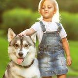 Petite fille avec un chien de traîneau de chien Photographie stock