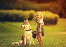 Petite fille avec un chien de traîneau de chien Photos libres de droits