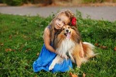 Petite fille avec un chien Sheltie Images stock