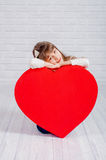 Petite fille avec un grand coeur Image stock