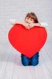 Petite fille avec un grand coeur Photo stock