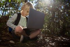 Petite fille avec un sac à dos se reposant sur la terre utilisant son ordinateur portable photo stock