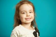 Petite fille avec un visage mignon, beaux yeux bruns, supports blancs comme neige de dents sur le fond d'isolement bleu image stock
